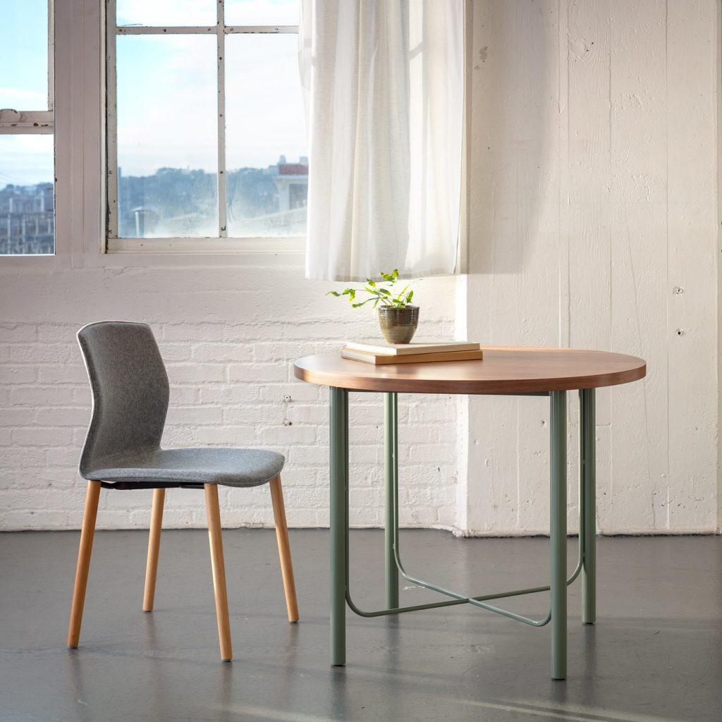 Table ronde devant une fenêtre avec une chaise grise AKABA