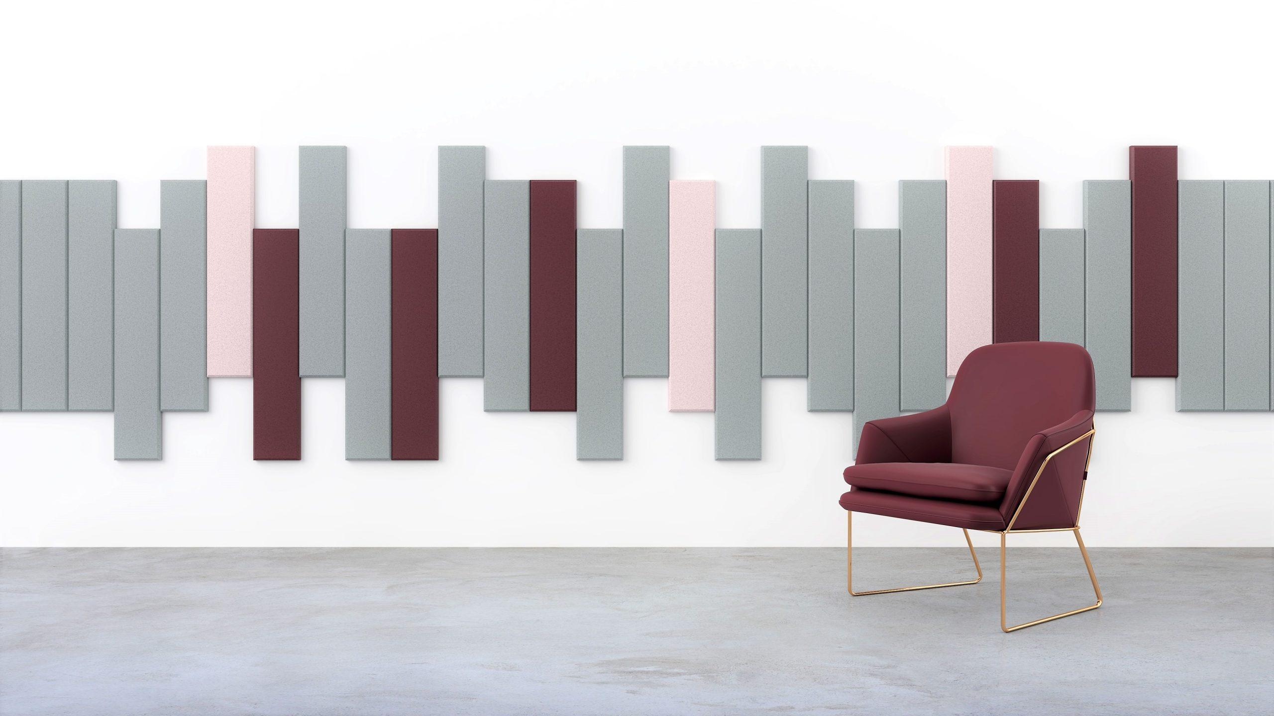 Fauteuil bordeau devant un mur de panneaux acoustiques gris, roses et bordeaux