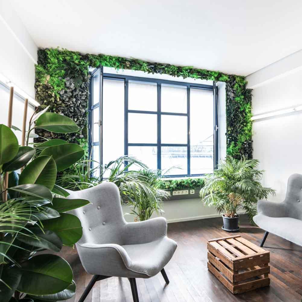 Fauteuil gris et caisse en bois devant une fenêtre végétalisée